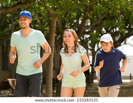 Cheerful family doing running outdoor and smiling - stock photo