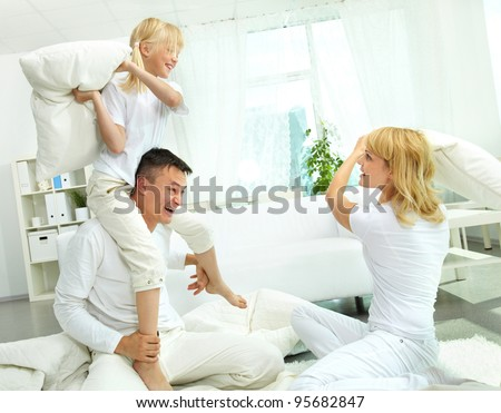 Cheerful family having a lot of fun fighting pillows - stock photo