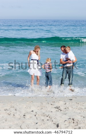 Cheerful family having fun on the sand at the beach