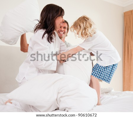 Cheerful family having pillow fight in a bedroom - stock photo