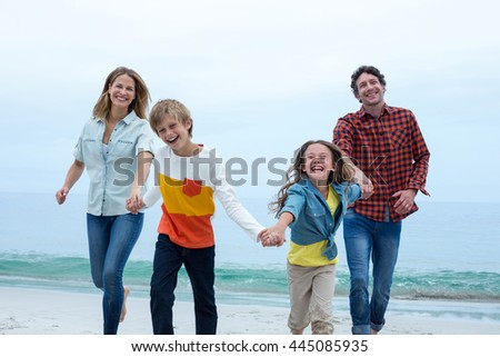 Cheerful family holding hands while running at sea shore - stock photo