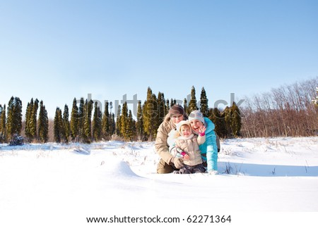 Cheerful family in snow - stock photo