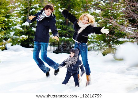 Cheerful family jumping in the winter forest