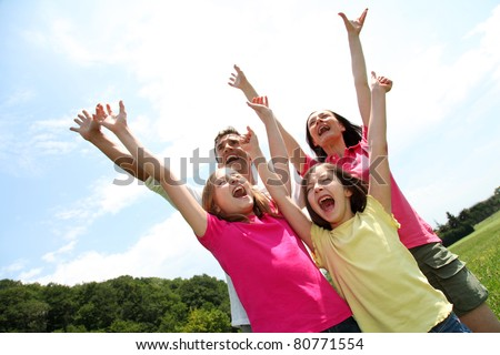 Cheerful family lifting arms up in the air - stock photo