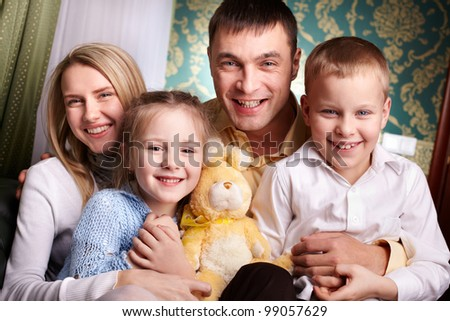 Cheerful family looking at camera - stock photo