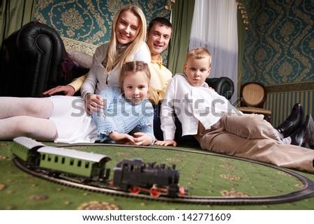 Cheerful family looking at camera at home - stock photo