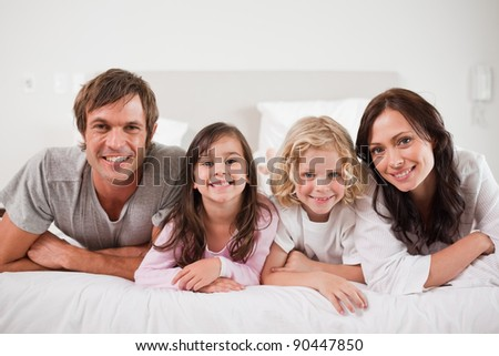 Cheerful family lying in a bed together - stock photo