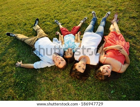 Cheerful family lying on beautiful summer meadow enjoying and having fun - stock photo