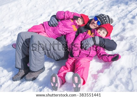 Cheerful family of father and two daughters lying on snow and smiling at camera - stock photo