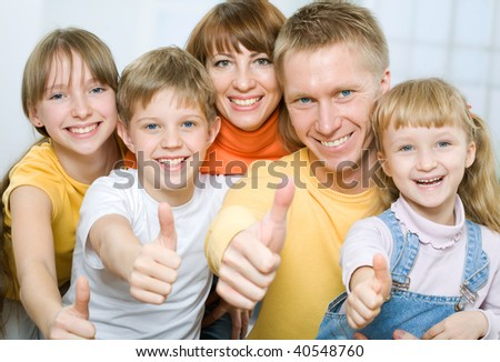 Cheerful family of five with their thumbs up - stock photo
