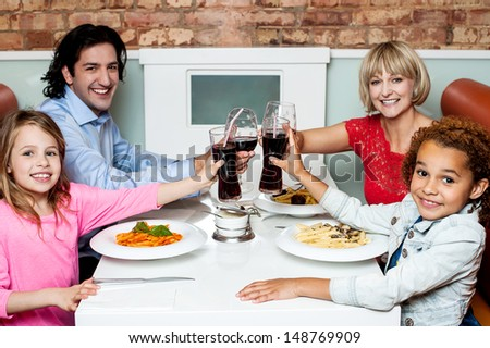 Cheerful family of four celebrating, Cheers! - stock photo