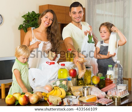 Cheerful family of four people with bags of food at home - stock photo