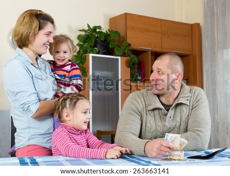 cheerful family of four planning budget and smiling indoors. Focus on man - stock photo