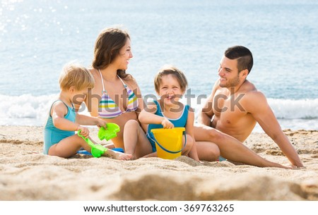 Cheerful family of four sitting on the beach and playing with sand