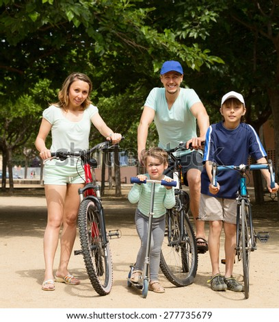 cheerful family of four walking in park with bicycles - stock photo