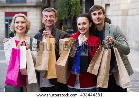 Cheerful family of four with shopping bags on city street - stock photo