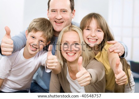 Cheerful family of four with their thumbs up - stock photo