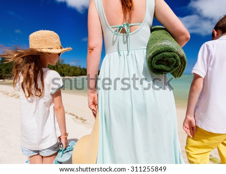 Cheerful family of mother and kids with towel and snorkeling equipment enjoying vacation at tropical beach - stock photo