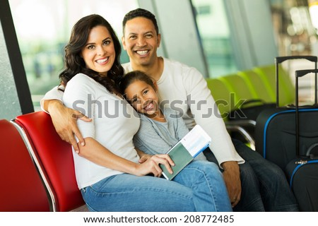 cheerful family of three at airport waiting for their flight - stock photo