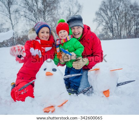 Cheerful family of three playing snow in the winter forest - stock photo
