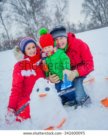 Cheerful family of three playing snow in the winter forest