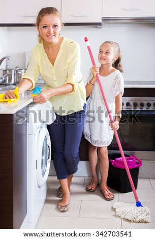 Cheerful family of two washing kitchen surfaces and smiling at home. Focus on the woman - stock photo