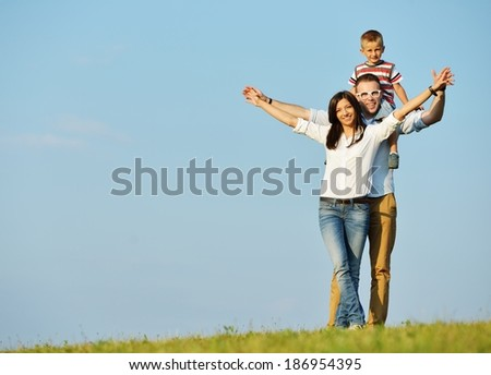 Cheerful family on beautiful summer meadow with sky in background - stock photo