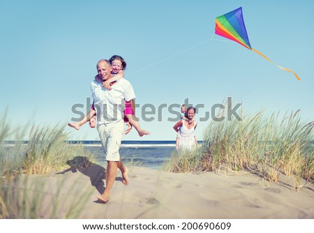 Cheerful Family Playing by the Beach - stock photo