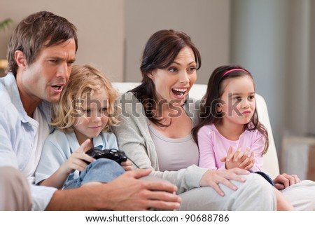 Cheerful family playing video games together in a living room - stock photo