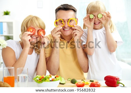 Cheerful family playing with vegetables in kitchen, healthy food - stock photo