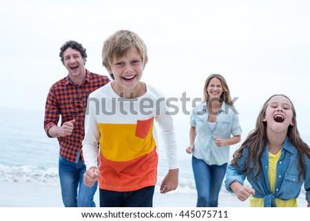 Cheerful family running at beach against sky - stock photo