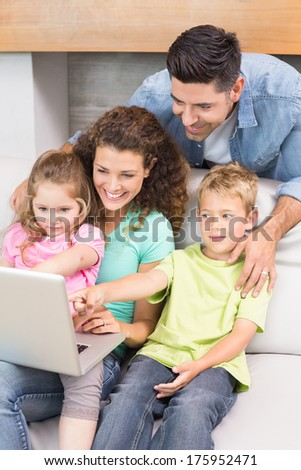 Cheerful family sitting on sofa looking at laptop at home in living room