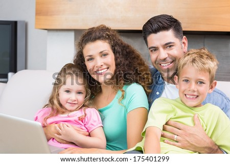 Cheerful family sitting on sofa with laptop at home in living room - stock photo