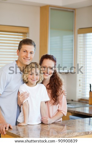 Cheerful family standing behind the kitchen counter together