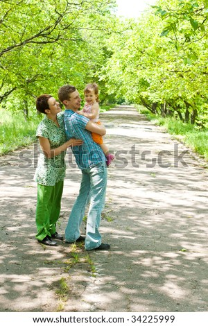Cheerful family standing in the park alley