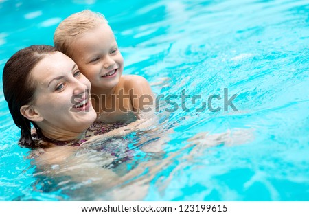 Cheerful family swimming in the pool to relax and have fun - stock photo