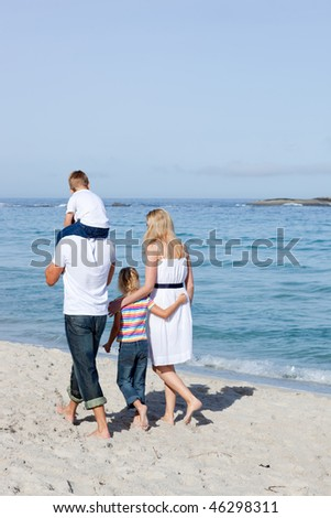 Cheerful family walking on the sand at the beach - stock photo