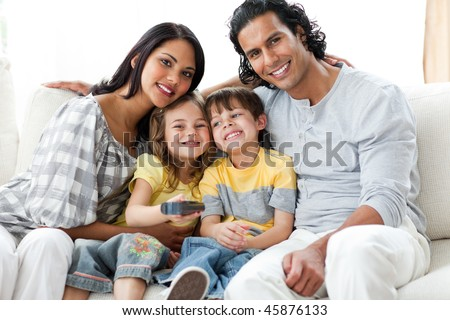 Cheerful family watching TV  together sitting on a sofa - stock photo