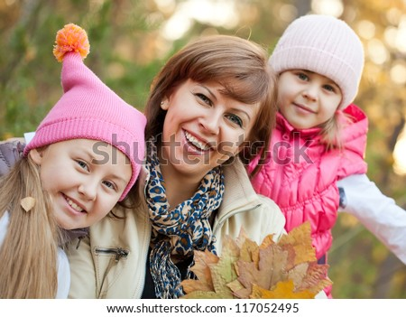 Cheerful family with leaves in autumnal park