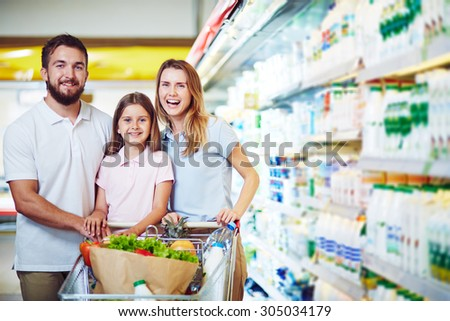 Cheerful family with shopping cart visiting supermarket