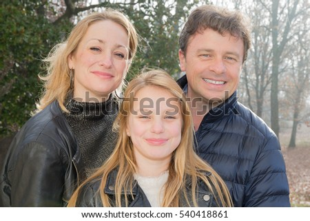 cheerful family with teenager and blonde mother with forties father in winter