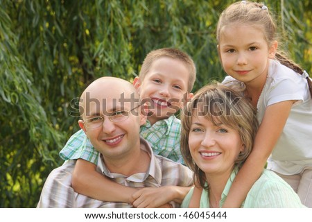 cheerful family with two children in early fall park. son is embracing father and daughter is embracing mother - stock photo