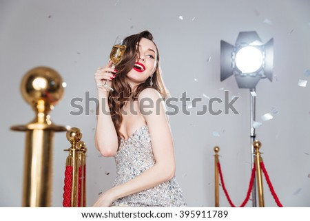 Cheerful famous woman holding glass of champagne - stock photo