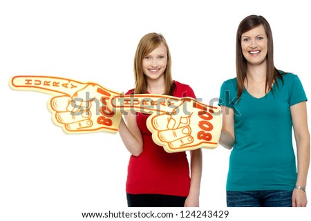 Cheerful fans pointing the big foam hand sideways. Half length portrait. - stock photo