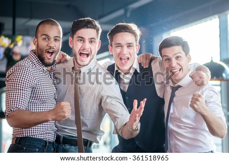 Cheerful fans watching TV and delight football. Four successful men shout and rejoice football meeting. Friends having fun together watching TV - stock photo