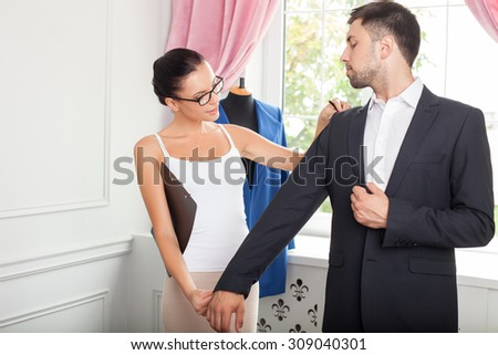 Cheerful fashion designer is working with her customer. She is standing near a man and touching a sleeve of his jacket. The woman is looking at it with concentration and smiling - stock photo
