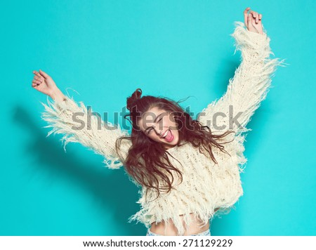 cheerful fashion girl going crazy making funny face and dancing. Blue color background.hipster style - stock photo