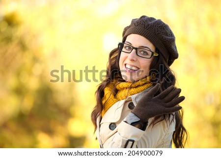 Cheerful fashion woman waving. Elegant girl wearing glasses and warm clothes in autumn. Beautiful brunette with eyewear, raincoat, wool cap and scarf doing hello gesture with hand. - stock photo