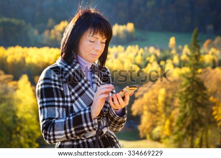 Cheerful fashion woman 40 years old wearing warm clothes in autumn. Beautiful brunette with autumn coat. Focus on her smartphone, write sms. Gold autumn background - stock photo