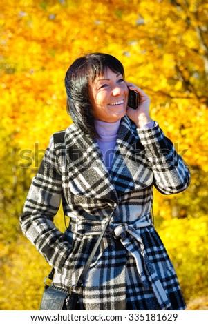 Cheerful fashion woman 40 years old wearing warm clothes in autumn. Beautiful brunette with autumn coat. Smiled and talking by cell phone, Gold autumn background - stock photo
